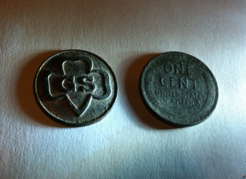 Girl Scout emblem and Lincoln cent side by side